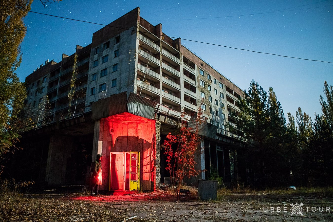 a stalker and an abandoned telephone booth at a corner at night