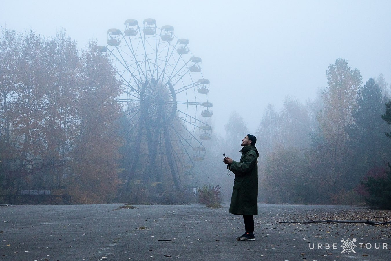 drone pilot next to Ferris wheel in abandoned city